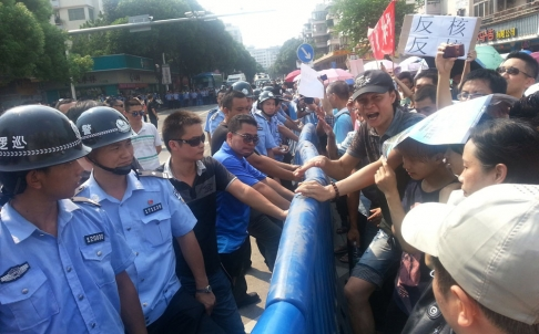 Police standing across demonstrators during a protest against plans for a uranium processing plant in Jiangmen. Photo: Reuters